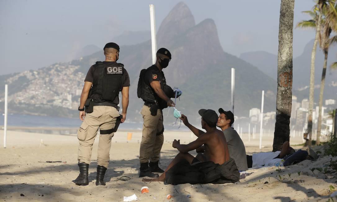 Pessoas em situação de rua recebem máscara de guarda municipal Foto: Marcia Foletto / Agência O Globo