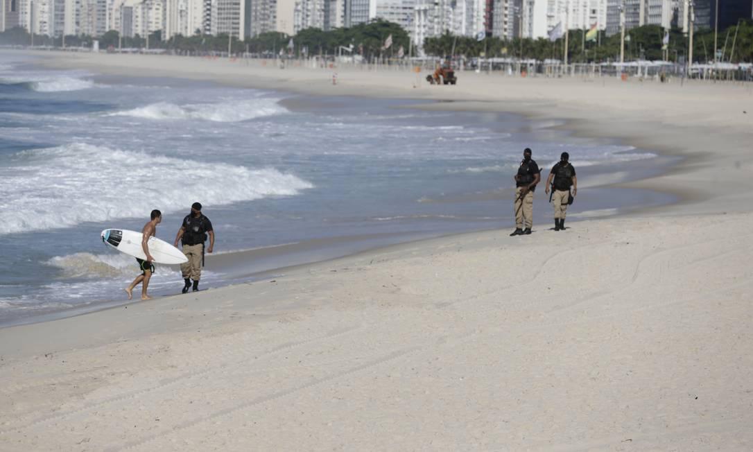 Guardas retiram surfista da praia. Novo decreto restringe, inclusive, prática esportiva individual nas praias Foto: Marcia Foletto / Agência O Globo