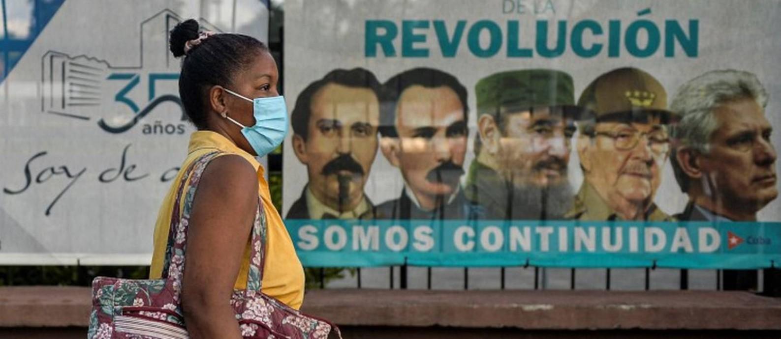 De máscara, mulher cubana caminha em frente a um mural com imagens de líderes cubanos Foto: YAMIL LAGE / AFP
