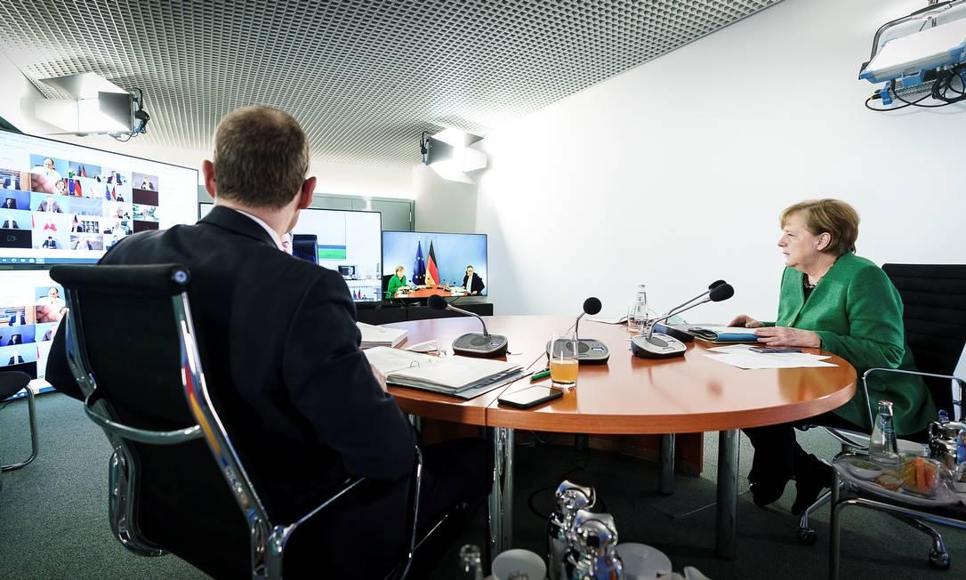 A chanceler alemã Angela Merkel e o prefeito de Berlim Michael Mueller participam de uma videoconferência com líderes estaduais na Chancelaria em Berlim Foto: JESCO DENZEL / via REUTERS