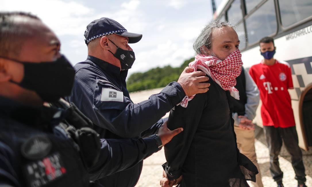 Manifestante é preso em Brasília após estender faixa que chamava o presidente Jair Bolsonaro de 'genocida': polícia invocou a Lei de Segurança Nacional, criticada por juristas Foto: UESLEI MARCELINO / REUTERS