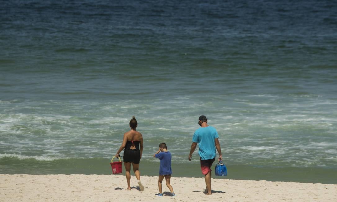 Casal, acompanhado de criança, fura restrição de banho de mar em praia do Rio Foto: Guito Moreto / Agência O Globo