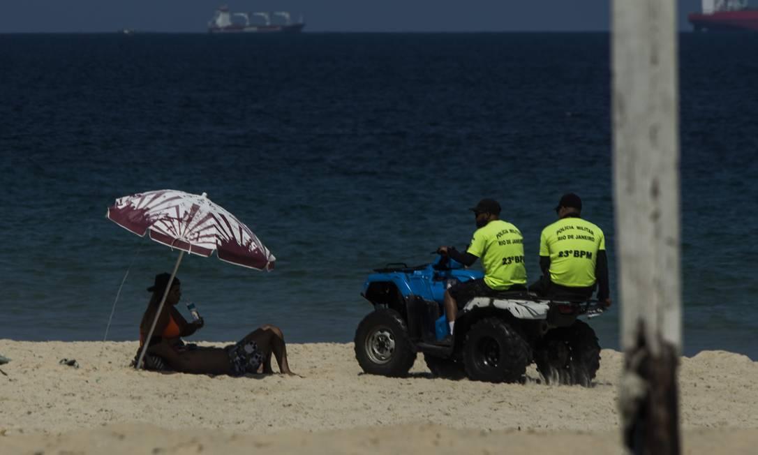 Polícia Mlitar dá apoio à fiscalização para fazer valer decreto que proíbe permanência na praia Foto: Guito Moreto / Agência O Globo