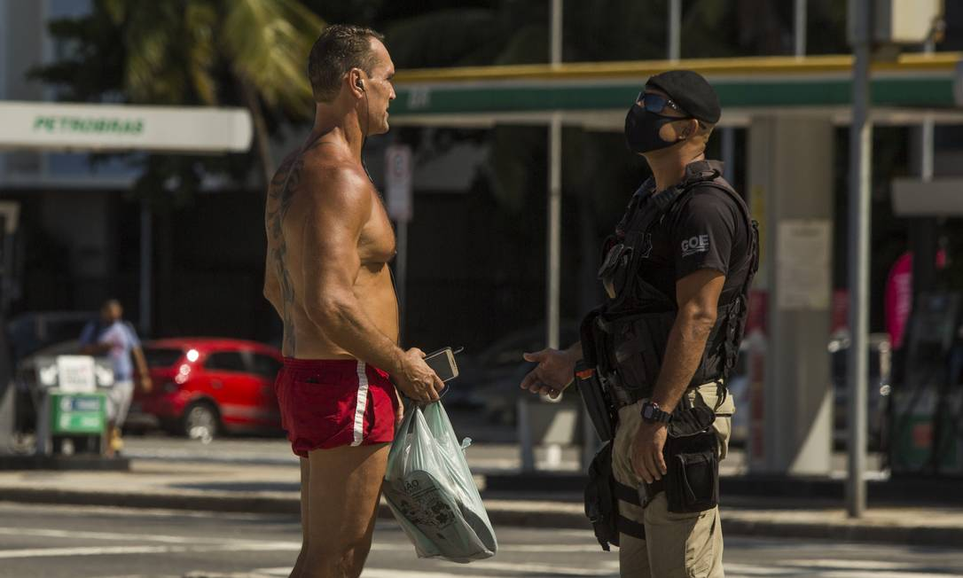 Guarda conversa com banhista que não respeitou decreto municipal que fecha as praias da cidade Foto: Guito Moreto / Agência O Globo