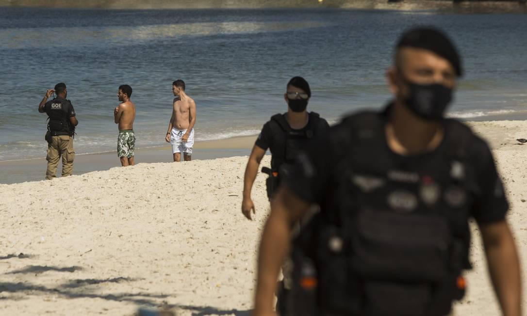 Guardas retiram banhistas que desrespeitam a restrição de acesso às praias Foto: Guito Moreto / Agência O Globo
