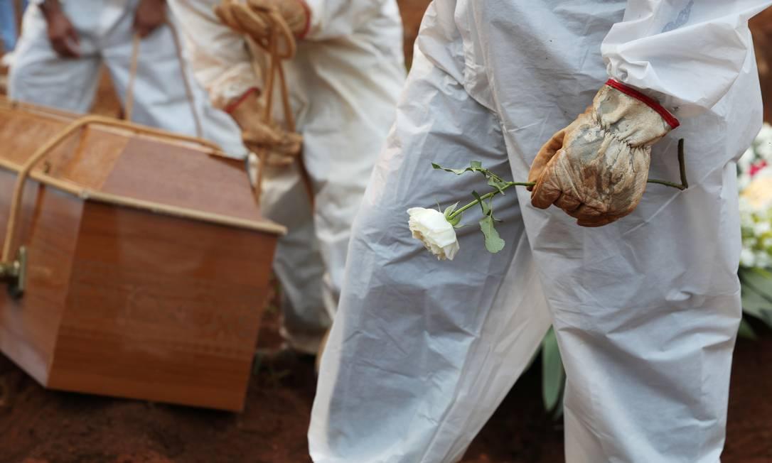 Coveiro com traje de proteção segura flor durante enterro de vítima da COVID-19, no cemitério Vila Formosa, em São Paulo Foto: AMANDA PEROBELLI / REUTERS
