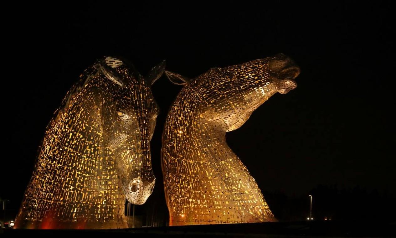 A escultura Kelpies, em Falkirk, Escócia, é iluminada em amarelo, como parte de um dia de reflexão para marcar o aniversário do primeiro bloqueio da pandemia Foto: RUSSELL CHEYNE / REUTERS