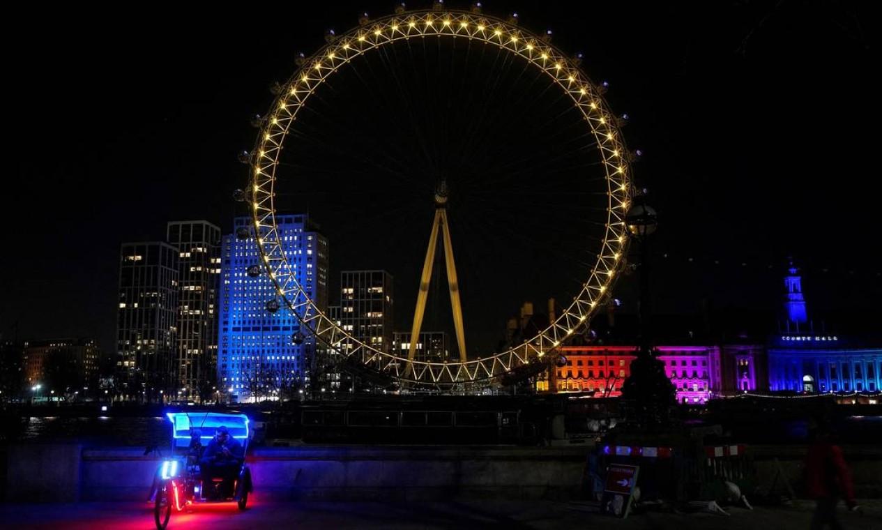 A roda-gigante London Eye, no centro de Londres, é iluminada em luz amarela Foto: NIKLAS HALLE'N / AFP