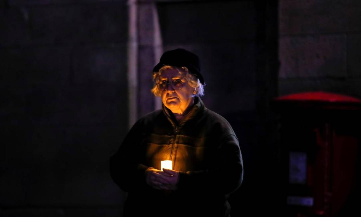 Mulher segura uma vela em frente à Catedral de Lichfield, como parte de um dia de reflexão para marcar o aniversário do primeiro bloqueio Foto: ANDREW BOYERS / REUTERS
