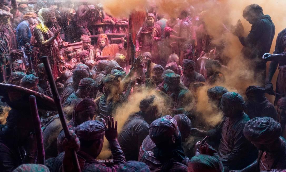 Pó colorido é jogado sobre devotos hindus em uma reunião tradicional durante as celebrações Lathmar Holi, o festival de cores da primavera, em um templo na vila de Barsana, no estado de Uttar Pradesh Foto: XAVIER GALIANA / AFP