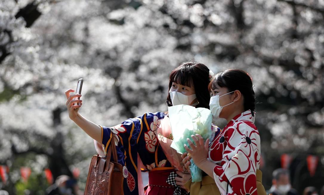 Com quimonos e máscaras, jovens japonesas passeiam pelo Parque Ueno, em Tóquio, durante a floração das cerejeiras Foto: ISSEI KATO / REUTERS