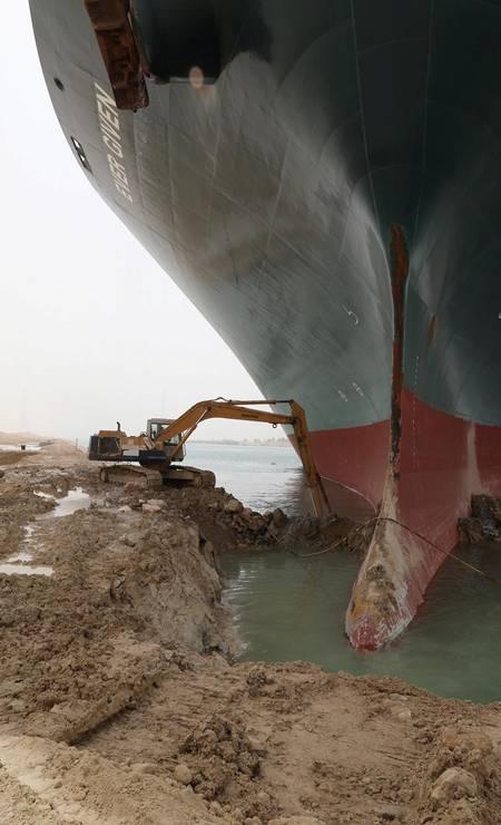 Escavadeira tenta libertar o navio: perto dele, parece de brinquedo Foto: HANDOUT / VIA REUTERS