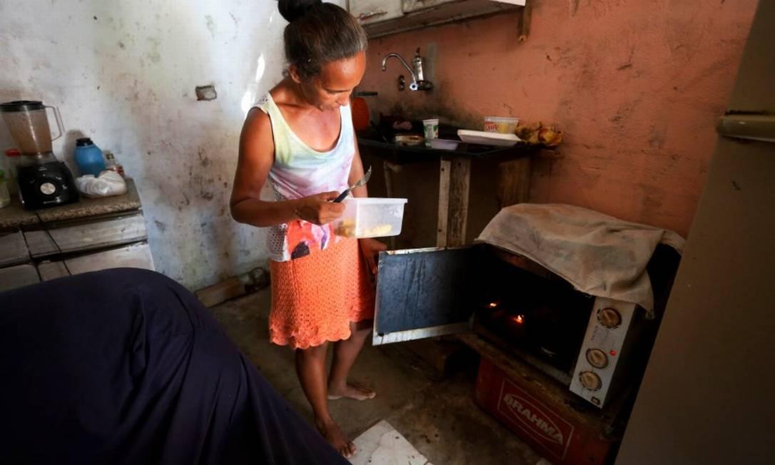 """Vanilza Maria da Silva Rodrigues cozinha em um forno elétrico que achou no lixo: """"Fazemos um bico aqui ou ali, mas não é o suficiente para comprar comida"""" Foto: Fabiano Rocha / Agência O Globo"""