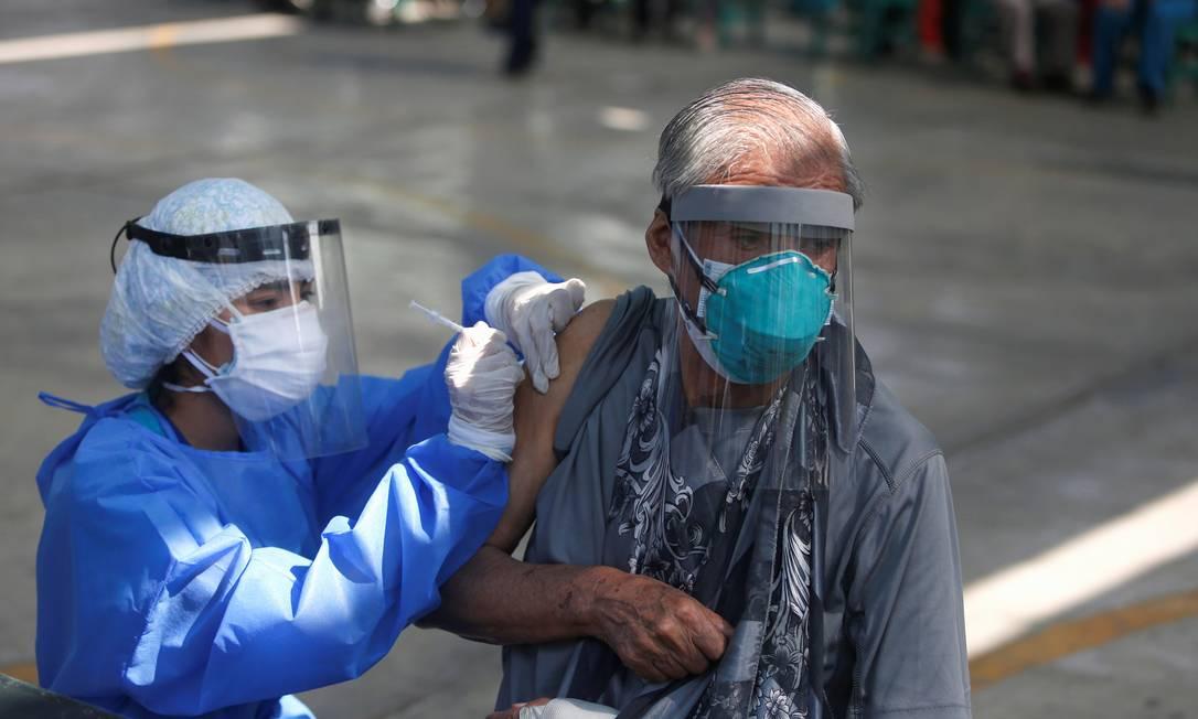 Idoso recebe dose da vacina da Pfizer-BioNTech em Lima, no Peru; imunização no país é considerada lenta, com índice de 2,2 vacinados por 100 mil habitantes Foto: SEBASTIAN CASTANEDA / REUTERS