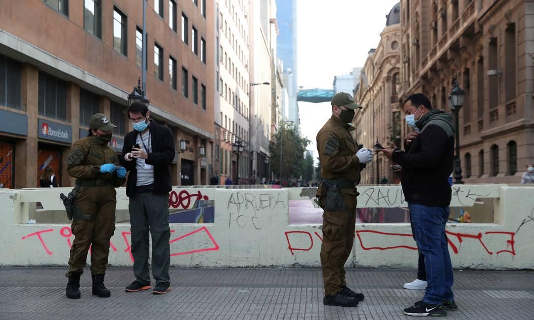 Policiais verificam salvaguardas em meio ao aumento das restrições durante o surto de coronavírus, em Santiago Foto: IVAN ALVARADO / REUTERS