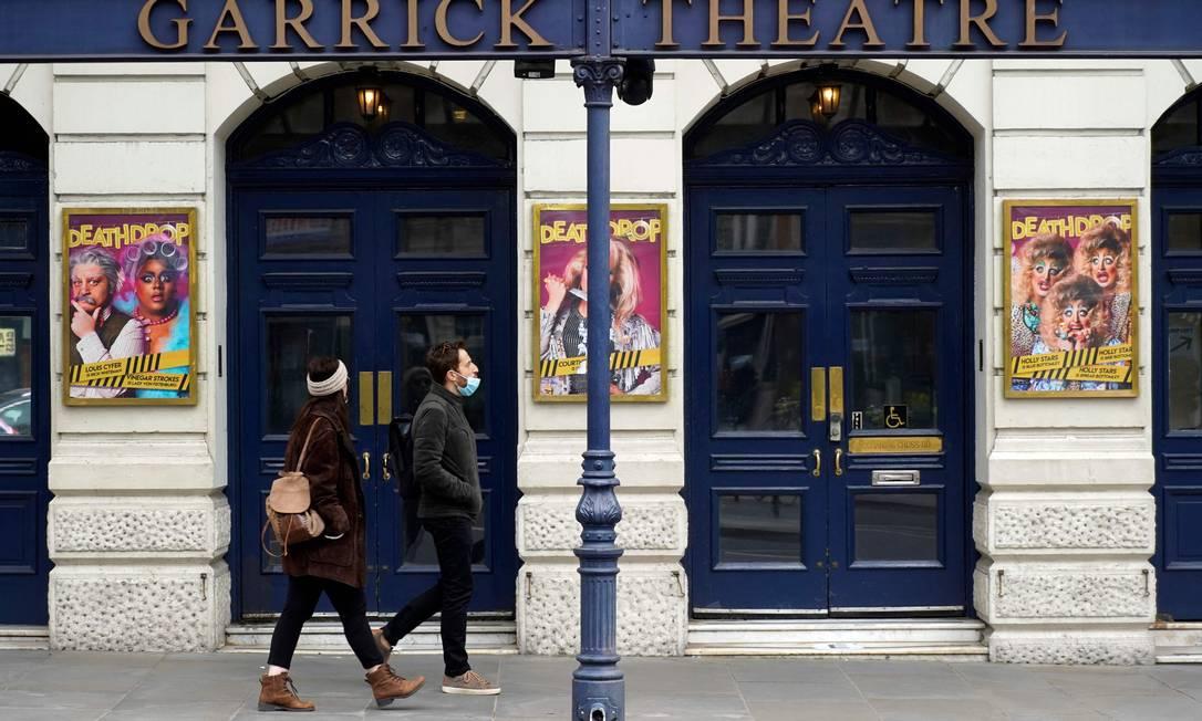 Pedestres passam por cinema fechado em Londres; segundo o cronograma de desconfinamento, casas de espetáculo só reabrem em maio, com lotação limitada Foto: NIKLAS HALLE'N / AFP/21-03-2021