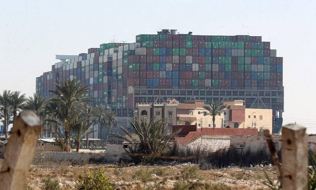 Prédios na frente do cargueiro gigante Ever Given, encalhado no Canal de Suez Foto: MOHAMED ABD EL GHANY / REUTERS