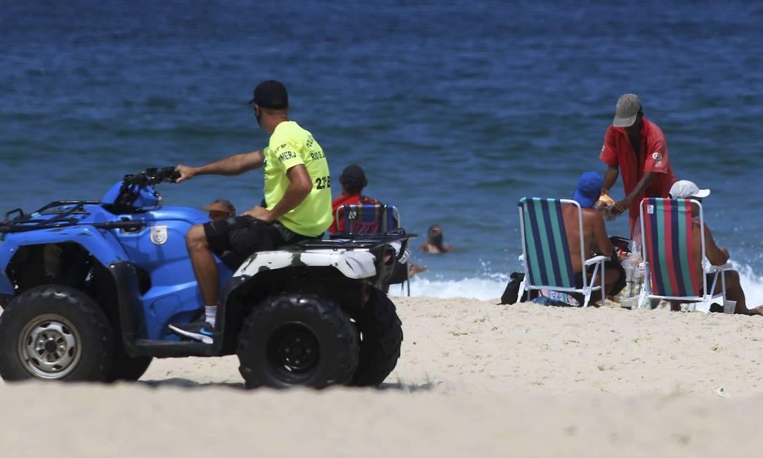 Ambulante vende seus produtos a banhistas em cadeira de praia diante de policiais que fiscalizam a praia do Leblon Foto: FABIANO ROCHA / Agência O Globo