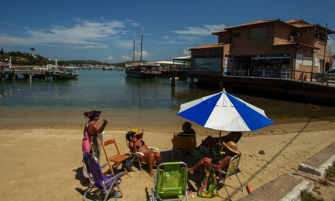 Flagrante de desrespeito à proibição de permanência na praia em plena Orla Bardot; ao fundo, turistas embarcam em passeio de barco, permitido Foto: Antônio Scorza / Agência O GLOBO