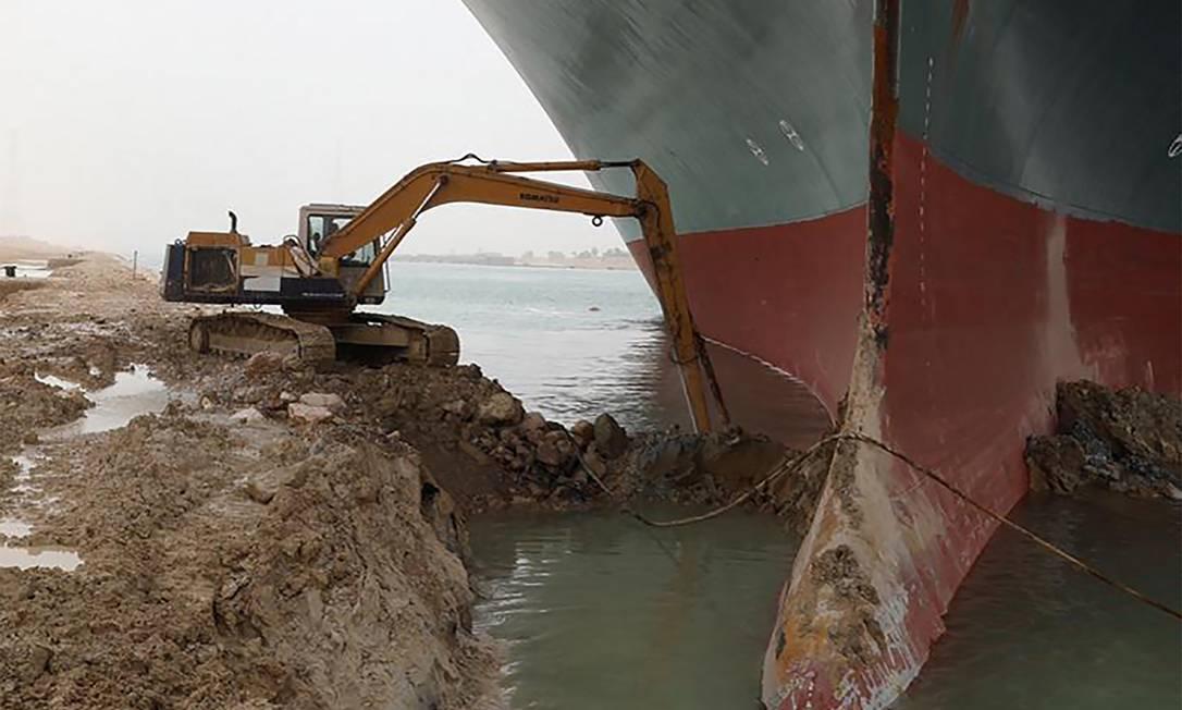 Escavadeira foi usada para liberar bulbo do navio, que atingiu a margem do Canal de Suez Foto: - / AFP