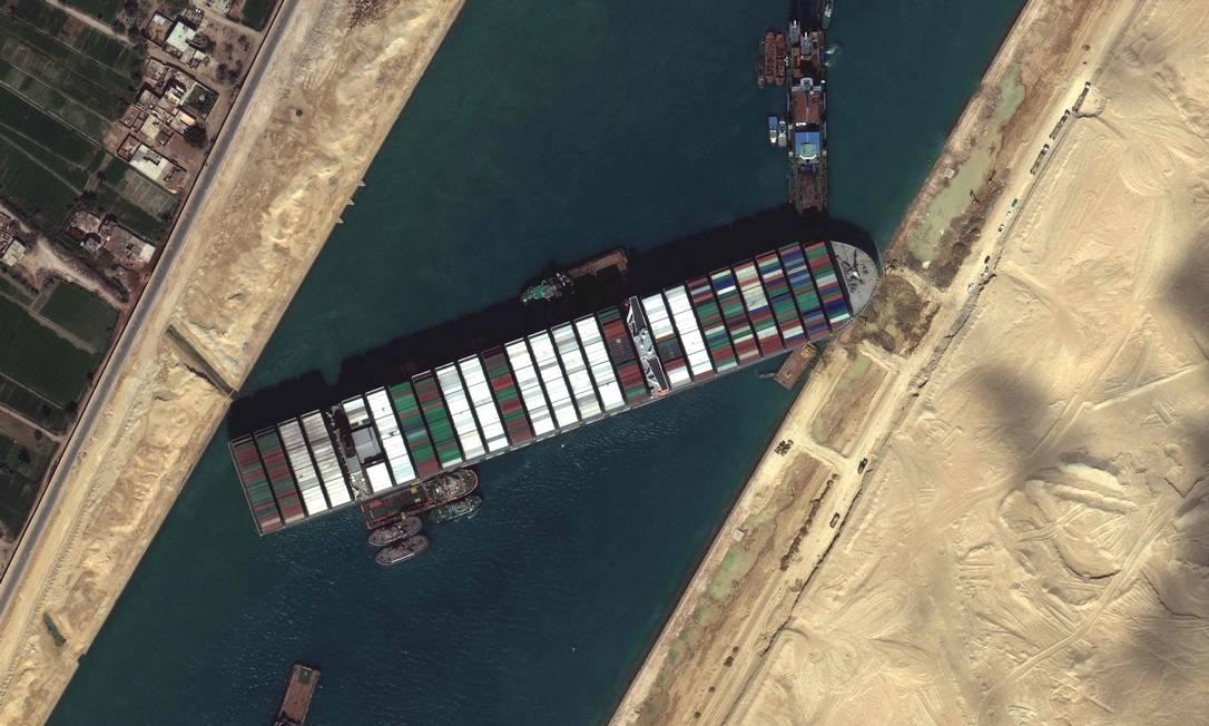 Rebocadores e dragas tentando libertar o navio que quase iniciou uma crise global de logística Foto: - / AFP