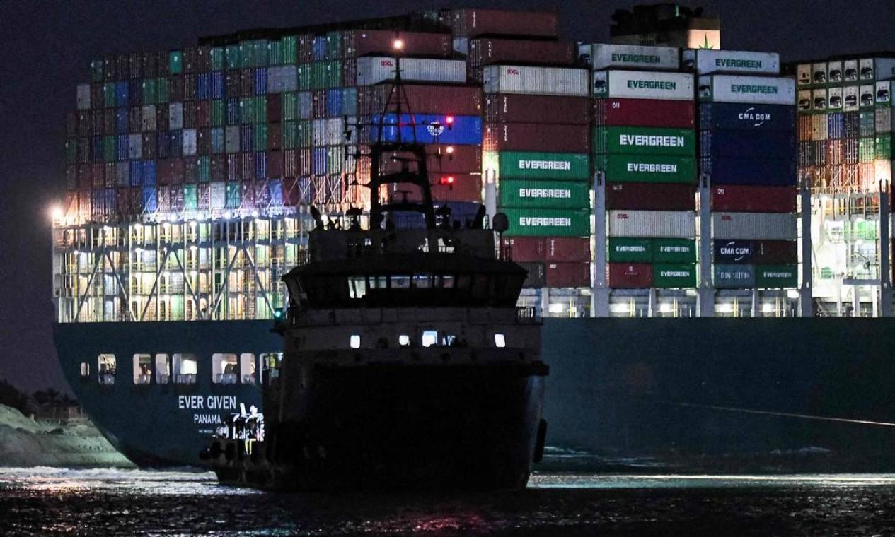 Rebocador trabalha durante a noite para desencalhar navio cargueiro gigante Foto: AHMED HASAN / AFP