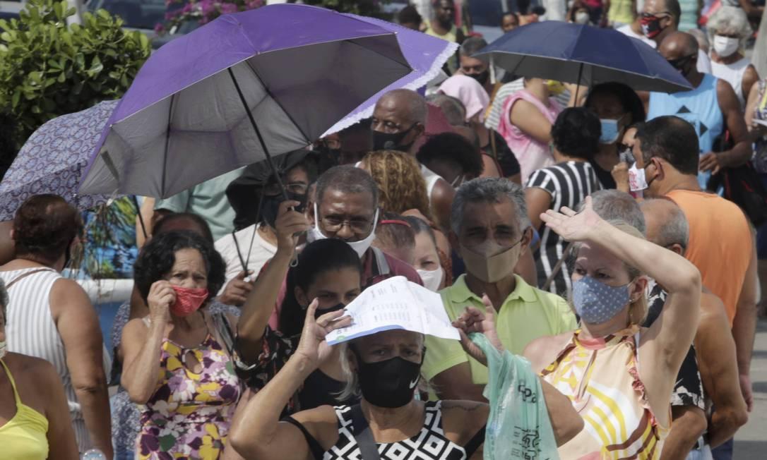 Idodos se protegem do sol enquanto enfrentam longo tempo de espera para se vacinar contra a Covid-19 Foto: Domingos Peixoto / Agência O Globo - 29/03/2021