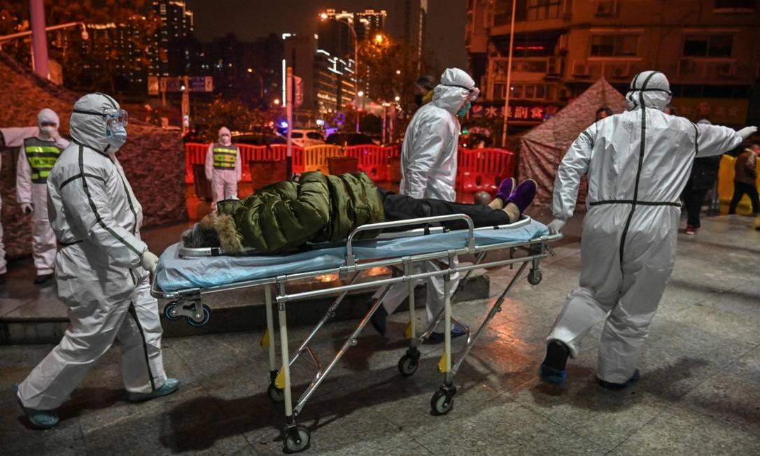 Foto de janeiro de 2020 mostra trabalhadores da linha de frente em Wuhan chegando com um paciente no hospital da Cruz Vermelha Foto: HECTOR RETAMAL / AFP/25-1-2020