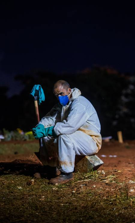 Coveiro usando EPI contra a Covid-19 descansa durante expediente noturno no cemitério Vila Formosa Foto: Edilson Dantas / Agência O Globo