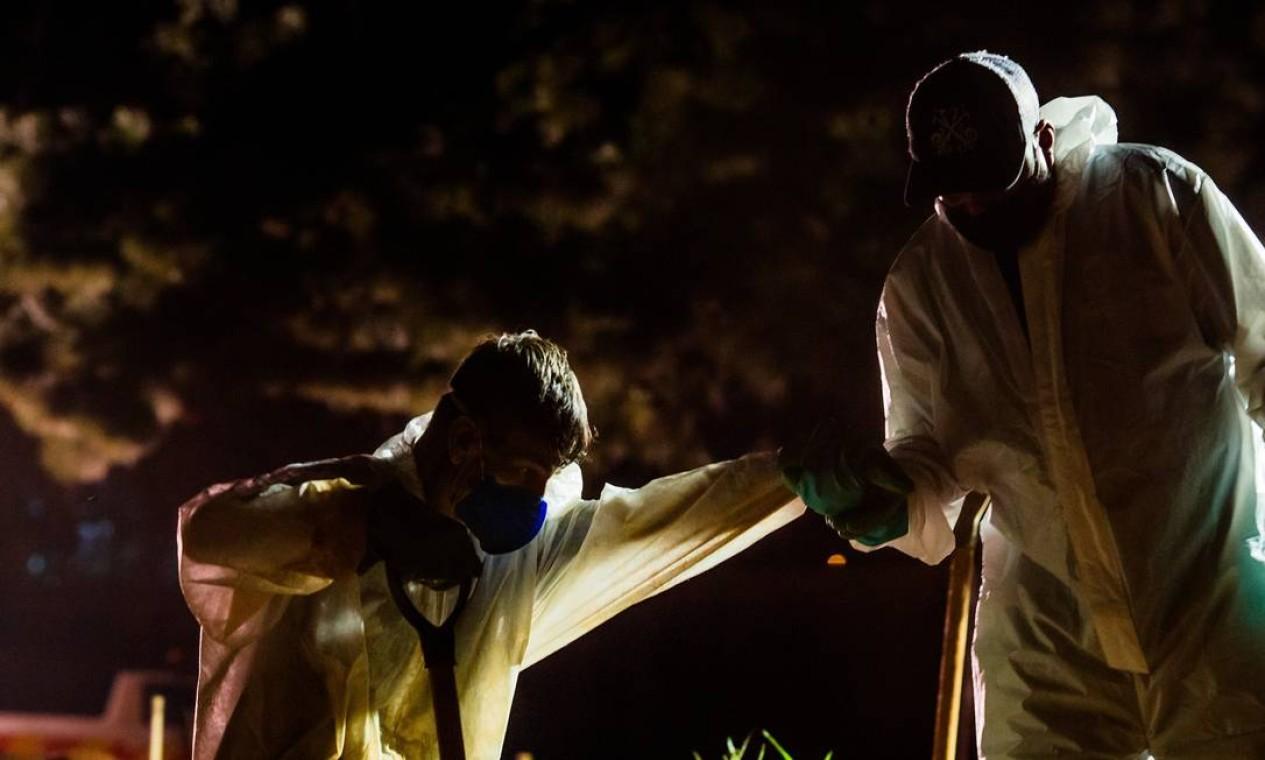 Trabalhador do cemitério Vila Formosa ajuda companheiro a sair de cova rasa Foto: Edilson Dantas / Agência O Globo