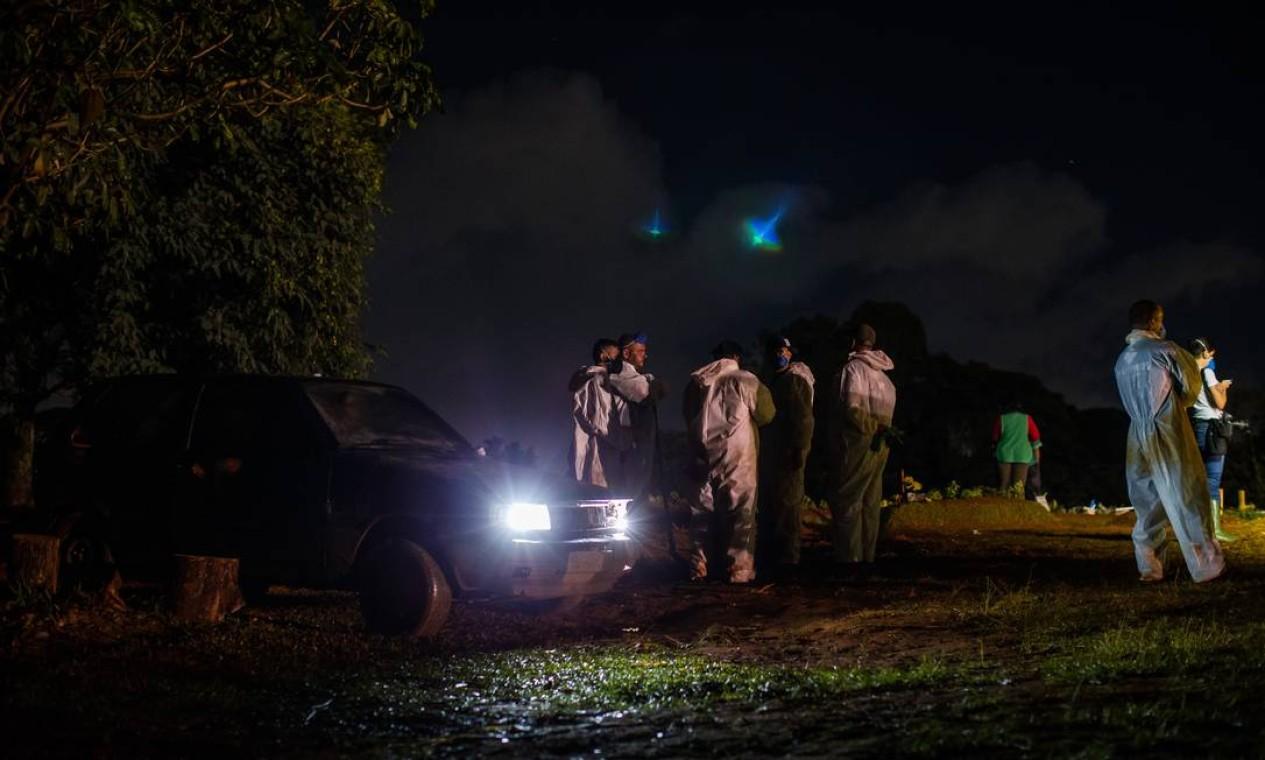 Carro particular é usado para ajudar na iluminação durante sepultamento noturno no cemitértio Vila Formosa Foto: Edilson Dantas / Agência O Globo