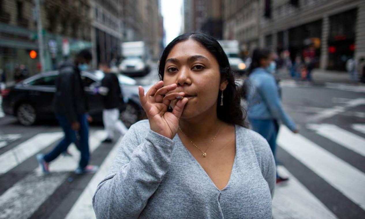 Eliana Miss Illi, gerente geral da Weed World, loja especializada em produtos canábicos, posa fuma um baseado na 7th Avenue Foto: KENA BETANCUR / AFP