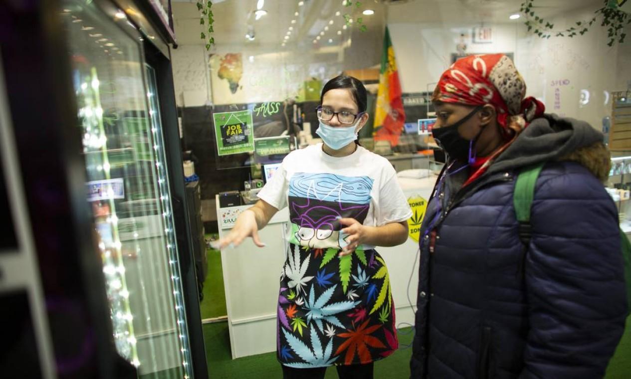 Cliente recebe informações sobre a maconha ao comprar folhas de THC na loja Weed World Foto: KENA BETANCUR / AFP