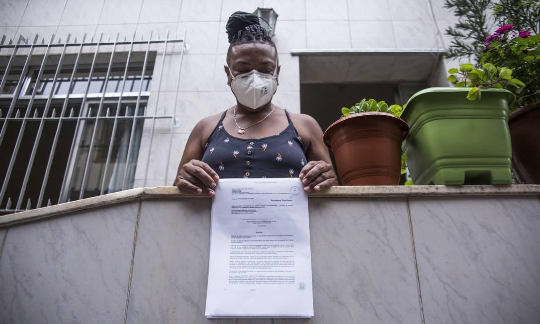 A enfermeira Adriana dos Santos exibe liminar que obteve junto à Defensoria do Estado para que sua mãe, Clarinda dos Santos, de 74 anos, fosse transferida para uma UTI Foto: Maria Isabel Oliveira / Agência O Globo
