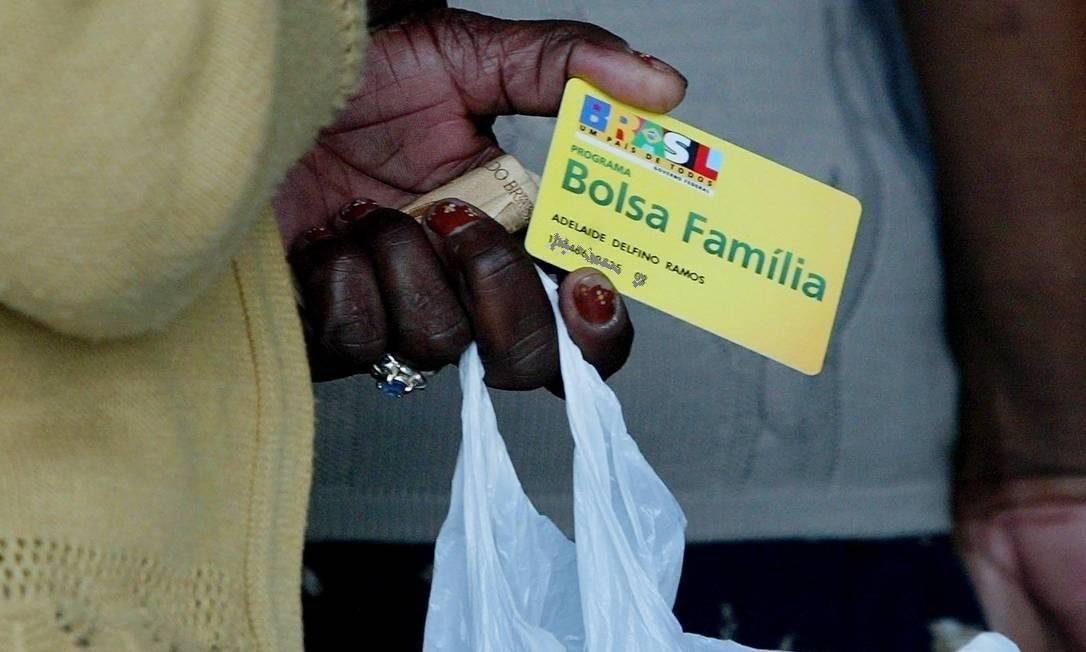 Beneficiária segura cartão do Bolsa Família Foto: Michel Filho / Agência O Globo