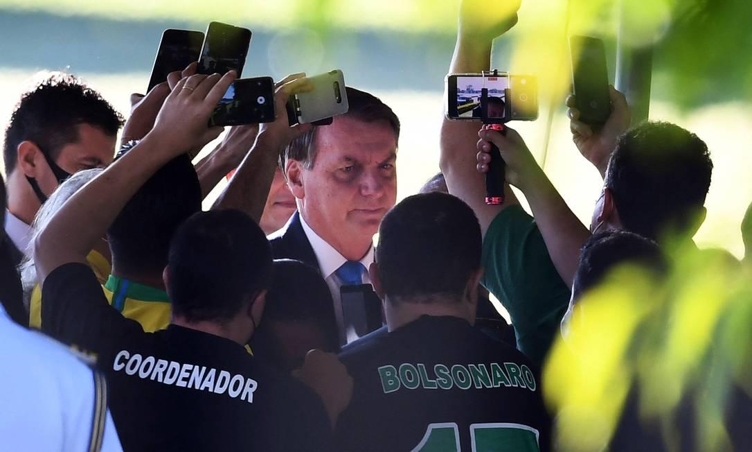 Mesmo depois de adotar um discurso pró-vacina, presidente brasileiro Jair Bolsonaro continuou com o comportamento negacionista, sem usar máscara de proteção e se aglomerando para falar com apoiadores ao deixar o Palácio da Alvorada, em Brasília Foto: Evaristo Sá / AFP - 31/03/2021