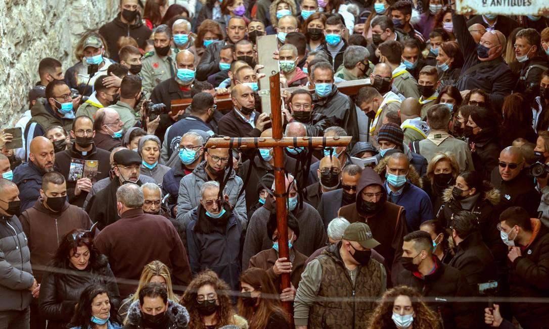 Fiéis cristãos carregam uma cruz de madeira ao longo do Caminho do Sofrimento, na Cidade Velha de Jerusalém, durante a procissão da Sexta-feira Santa Foto: EMMANUEL DUNAND / AFP