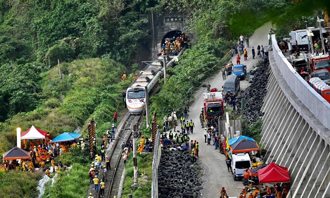 Equipes de resgate no local onde um trem descarrilou dentro de um túnel nas montanhas de Hualien, leste de Taiwan Foto: SAM YEH / AFP