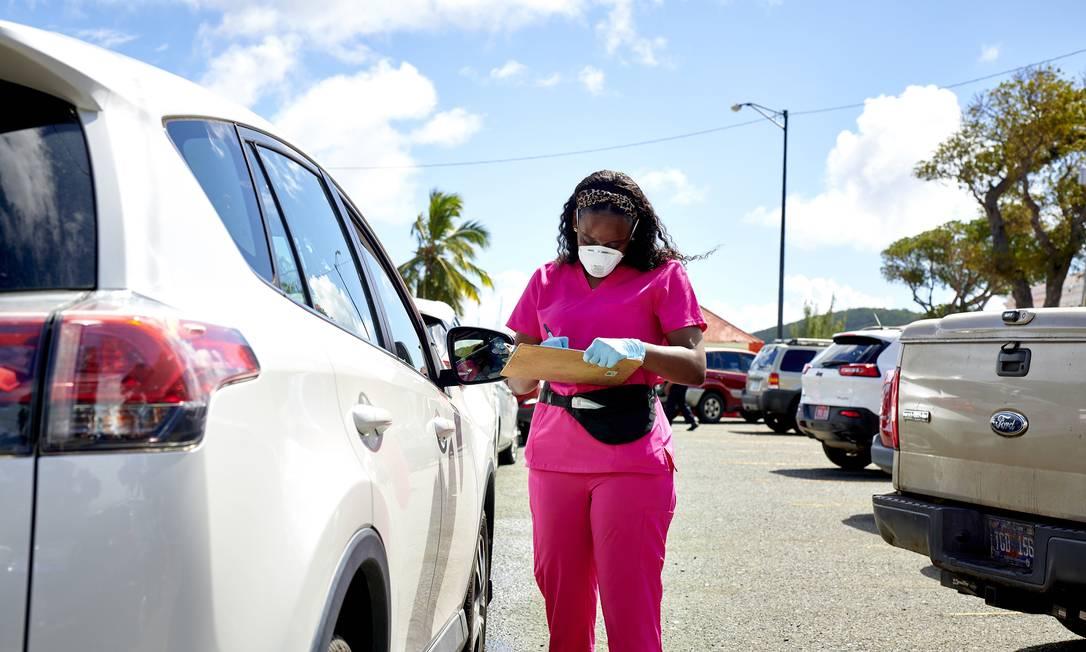Uma profissional da saúde se prepara para administrar testes para Covid-10 num drive-thru em Charlotte Amalie, nas Ilhas Virgens Americana Foto: Gabby Jones / The New York Times