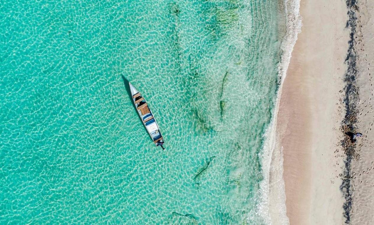 Barquinho de pescador entre a água azul-turquesa e a areia muito clara da Praia de Shoab, na Ilha de Socotra, no Iêmen Foto: - / AFP