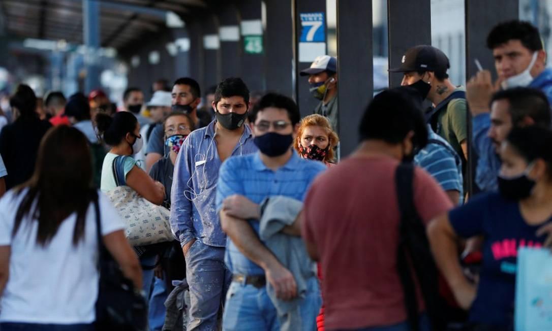 De máscara, argentinos esperam em ponto de ônibus em Buenos Aires Foto: AGUSTIN MARCARIAN / REUTERS/31-3-21