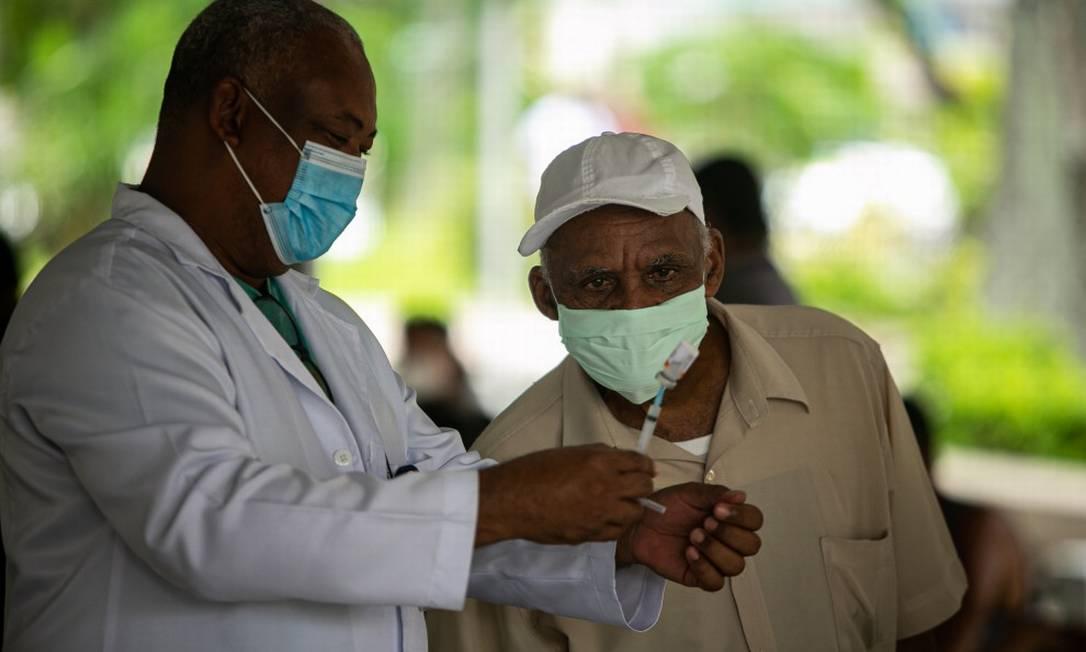 Idoso observa atento a profissional retirando o líquido da vacina na Uerj Foto: Hermes de Paula / Agência O Globo