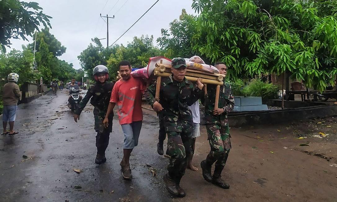 Aldeões carregam o corpo de uma vítima das enchentes em Lembata, East Flores. Inundações e deslizamentos de terra que mataram mais de 100 pessoas e deixaram dezenas de desaparecidos na Indonésia e no vizinho Timor Leste Foto: HANDRIANUS EMANUEL / AFP