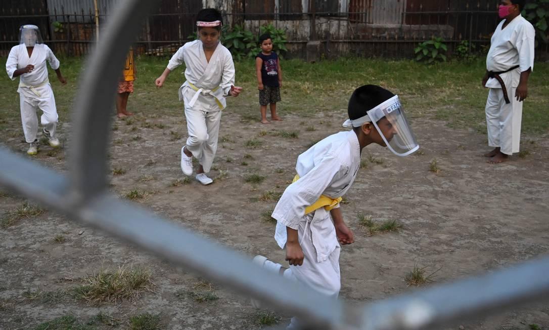 Crianças usando escudos faciais em meio às preocupações com a disseminação do coronavírus Covid-19, aquecem durante uma aula de treinamento de artes marciais, em Calcutá, Índia Foto: DIBYANGSHU SARKAR / AFP