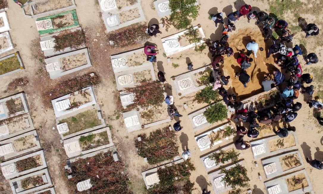 Imagem de drone mostra palestinos enterrando o corpo de um homem, vítima da COVID-19, em um cemitério no centro da Faixa de Gaza. A Palestina acumula 2.716 mortos na pandemia Foto: MOHAMMED SALEM / REUTERS