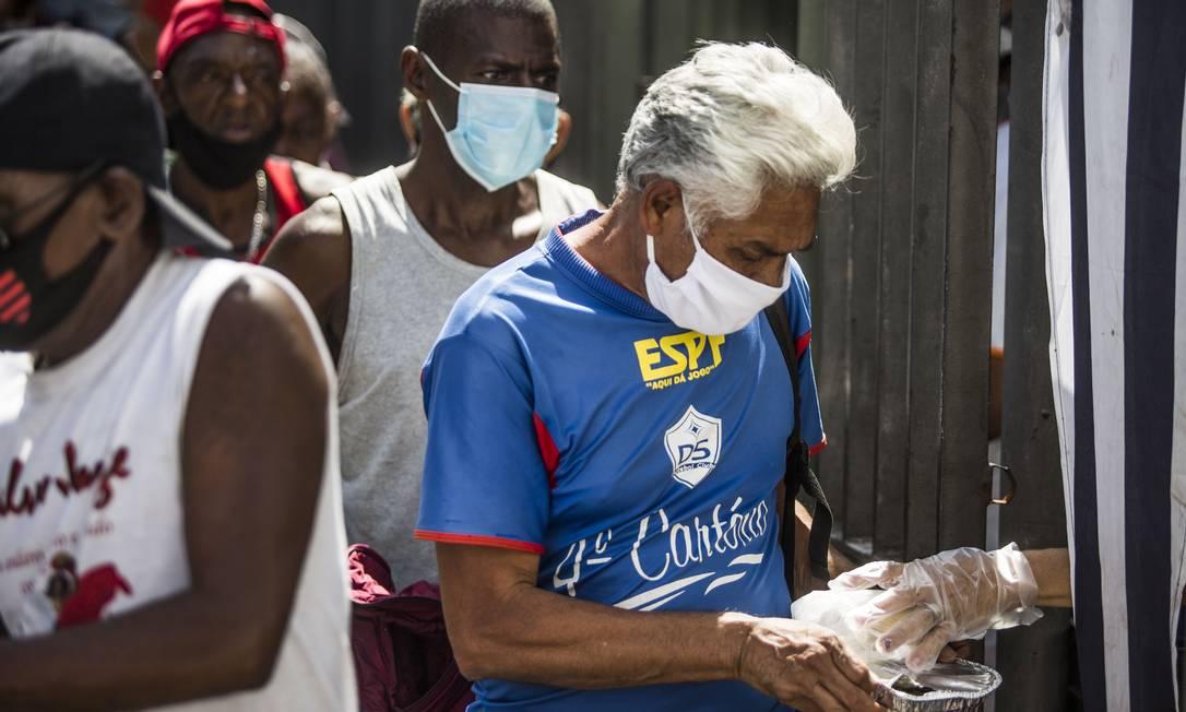 Homem usando máscara de proteção recebe refeição no Centro do Rio Foto: Guito Moreto / Agência O Globo