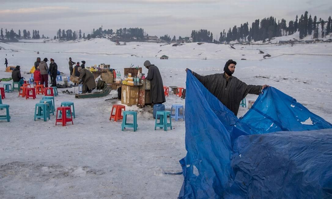 Vendedores guardam suas barraquinhas de comida e bebida no momento em que a neve começa a cair, na estação de Gulmarg, aos pés do Himalaia Foto: Showkat Nanda / The New York Times