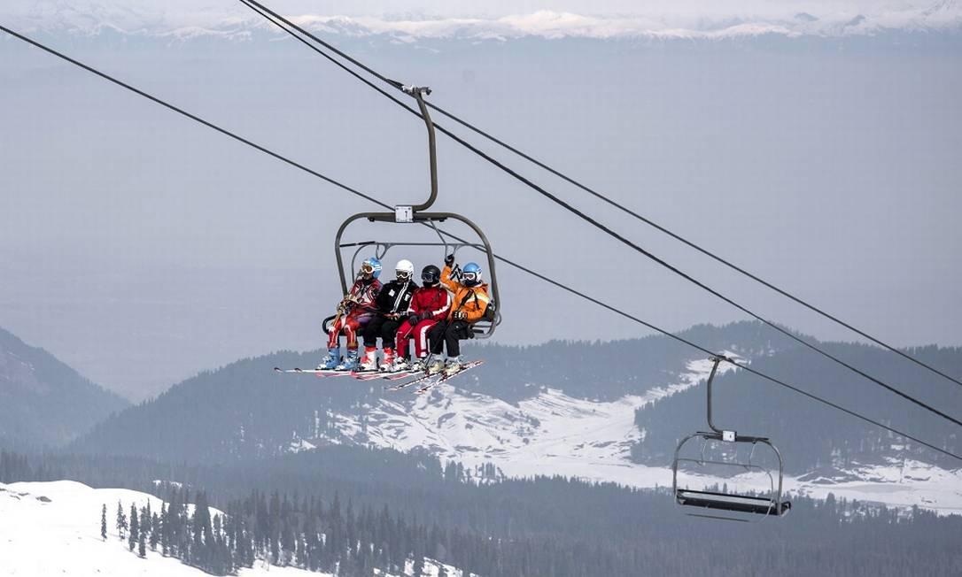 Esquiadores num teleférico sobem até o topo de uma das pistas da estação de Gulmarg, na Caxemira Foto: Showkat Nanda / The New York Times