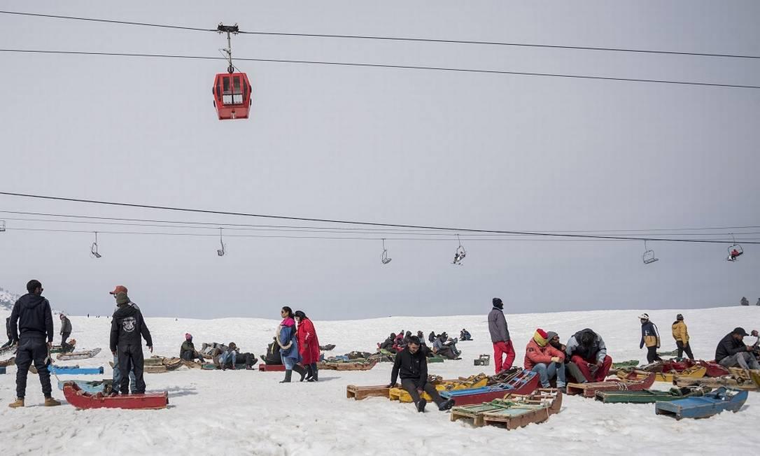 Homens esperam clientes para alugar seus trenós de neve na estação de esqui de Gulmarg, no norte da Índia Foto: Showkat Nanda / The New York Times