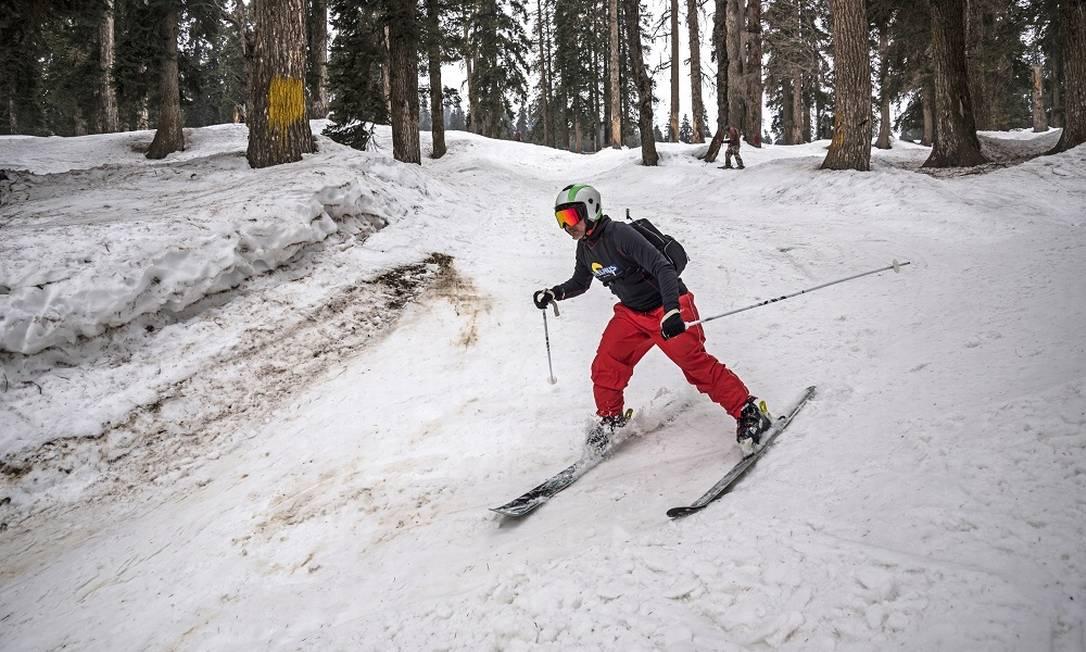 Esquiador desce uma pista num bosque na estação de Gulmarg, na Índia Foto: Showkat Nanda / The New York Times